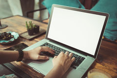 Jovem mulher que usa o portátil na cafetaria Fotografia de Stock Royalty Free
