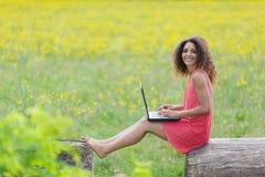 Jovem mulher que usa o portátil na natureza Imagens de Stock