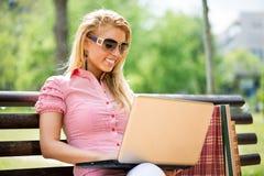 Jovem mulher que usa o portátil no parque Fotos de Stock