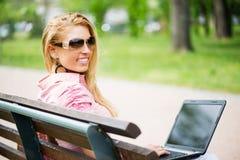Jovem mulher que usa o portátil no parque Foto de Stock Royalty Free
