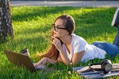 Jovem mulher que usa o portátil no parque que encontra-se na grama verde Conceito da atividade do tempo de lazer imagens de stock royalty free