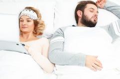Jovem mulher que usa o portátil quando seu marido dormir fotografia de stock