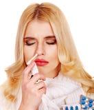 Jovem mulher que usa o pulverizador da garganta. Imagens de Stock