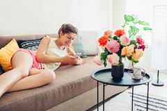 Jovem mulher que usa o smartphone que encontra-se no sofá em casa Sala de visitas decorada com o ramalhete das rosas imagem de stock royalty free