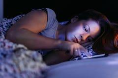 Jovem mulher que usa o smartphone na cama na noite fotografia de stock royalty free
