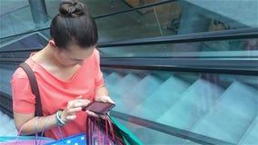 Jovem mulher que usa o smartphone na escada rolante no shopping e usando o telefone esperto Estilo de vida urbano, permanecendo e video estoque