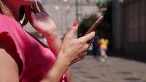 Jovem mulher que usa o smartphone na rua Fêmea, telefone celular, chating filme