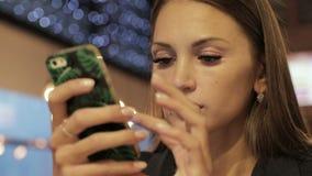 Jovem mulher que usa o smartphone no café filme