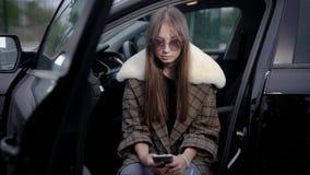 Jovem mulher que usa o smartphone no carro video estoque