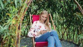 Jovem mulher que usa o smartphone no miradouro da planta video estoque
