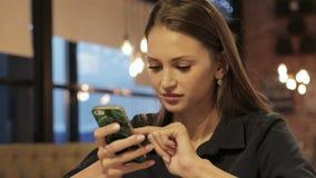 Jovem mulher que usa o smartphone no restaurante vídeos de arquivo