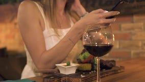 Jovem mulher que usa o smartphone quando jantar no restaurante de assado Redes da consultação da mulher pelo telefone celular na  video estoque