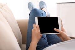 Jovem mulher que usa o tablet pc ao descansar no sofá em casa foto de stock
