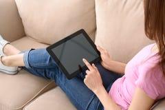 Jovem mulher que usa o tablet pc para a entrega em linha do alimento ao descansar no sofá dentro foto de stock