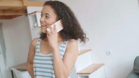 Jovem mulher que usa o telefone celular em casa video estoque