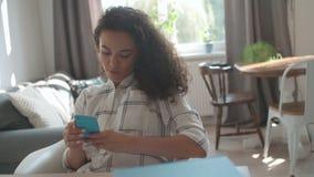 Jovem mulher que usa o telefone celular em casa vídeos de arquivo