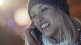 Jovem mulher que usa o telefone celular em uma cidade na noite video estoque