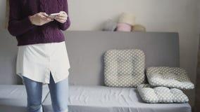 Jovem mulher que usa o telefone celular na sala home Mensagem de datilografia da menina no smartphone video estoque