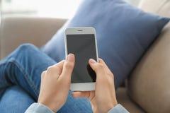 Jovem mulher que usa o telefone celular para a entrega em linha do alimento ao descansar no sofá dentro fotos de stock