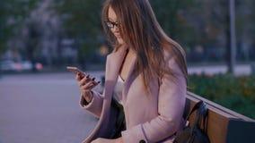 Jovem mulher que usa o telefone celular que senta-se no banco em nivelar a cidade moderna do parque vídeos de arquivo