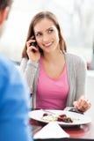 Mulher que usa o telefone móvel no restaurante imagens de stock royalty free