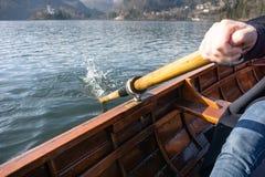 Jovem mulher que usa a pá em um barco de madeira com a ilha sangrada atrás dela - enfileiramento sangrado lago do Eslovênia em ba fotografia de stock
