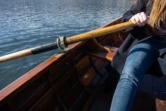 Jovem mulher que usa a pá em um barco de madeira - enfileiramento sangrado lago do Eslovênia em barcos de madeira imagem de stock
