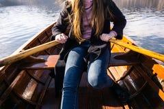 Jovem mulher que usa a pá em um barco de madeira - enfileiramento sangrado lago do Eslovênia em barcos de madeira fotos de stock