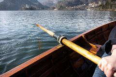 Jovem mulher que usa a pá em um barco de madeira - enfileiramento sangrado lago do Eslovênia em barcos de madeira foto de stock royalty free