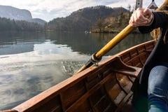 Jovem mulher que usa a p? em um barco de madeira com a ilha sangrada atr?s dela - enfileiramento sangrado lago do Eslov?nia em ba foto de stock