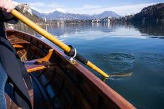 Jovem mulher que usa a p? em um barco de madeira com o castelo sangrado atr?s dele - enfileiramento sangrado lago do Eslov?nia em fotos de stock