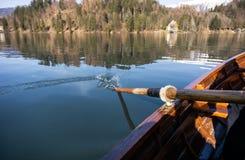 Jovem mulher que usa a p? em um barco de madeira - enfileiramento sangrado lago do Eslov?nia em barcos de madeira imagem de stock royalty free