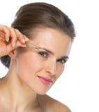 Jovem mulher que usa a pinça na testa Fotografia de Stock