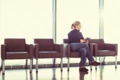Jovem mulher que usa seu PC digital da tabuleta em uma sala de estar do aeroporto, sala de espera moderna, com luminoso Foto de Stock