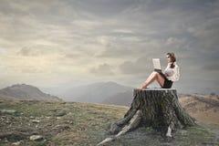 Jovem mulher que usa seu portátil Foto de Stock Royalty Free
