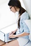 Jovem mulher que usa seu portátil em casa Imagens de Stock