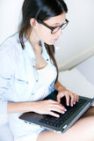 Jovem mulher que usa seu portátil em casa Fotos de Stock Royalty Free