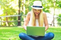 Jovem mulher que usa seu portátil fora foto de stock royalty free