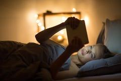 Jovem mulher que usa seu tablet pc em sua cama imagens de stock