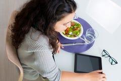 Jovem mulher que usa a tabuleta ao comer Foto de Stock Royalty Free