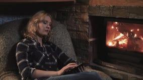 Jovem mulher que usa a tabuleta de Digitas que senta-se pela chaminé em casa filme