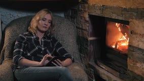 Jovem mulher que usa a tabuleta de Digitas que senta-se pela chaminé em casa vídeos de arquivo