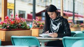 Jovem mulher que usa a tabuleta digital no café da rua filme