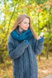 Jovem mulher que usa um móbil fora no outono Imagens de Stock Royalty Free