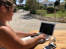 Jovem mulher que usa um portátil fora fotografia de stock royalty free