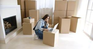 Jovem mulher que usa um portátil em uma caixa de cartão Fotografia de Stock Royalty Free