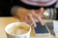 Jovem mulher que usa um smartphone ao sentar-se em um café, café delicioso das bebidas blurry imagens de stock royalty free