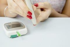Jovem mulher que usa uma pena da lanceta em seu dedo imagem de stock