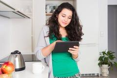 Jovem mulher que usa uma tabuleta em sua cozinha Fotografia de Stock Royalty Free