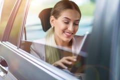 Jovem mulher que usa uma tabuleta em um carro imagens de stock